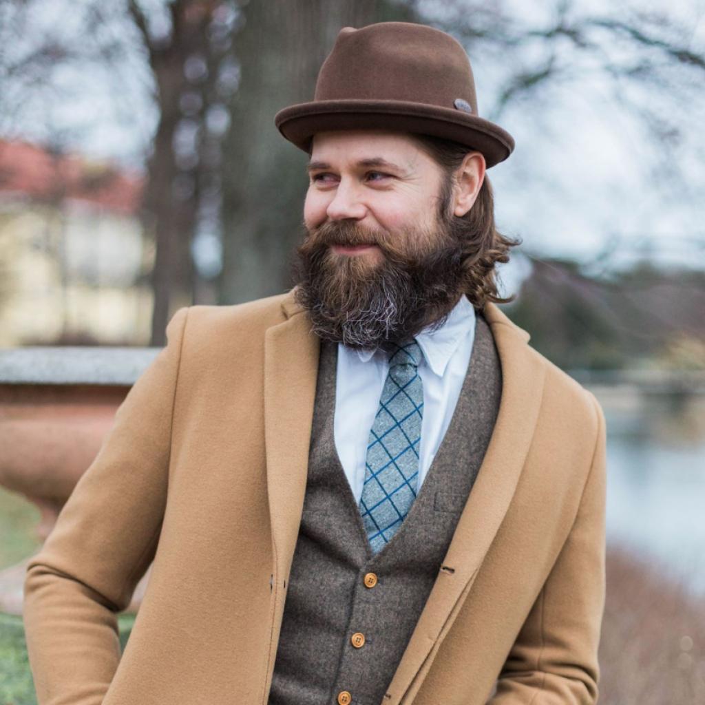 stilig karl i hatt lutar sig mot ett räcke i en park
