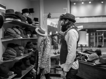 En man och en kvinna är på besök hos Malmös äldsta hattbutik och testar diverse huvudbonader