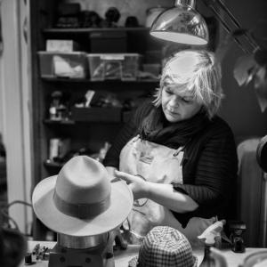 Modist jobbar på en hatt i hattbutik westerblads hattverkstad i Malmö